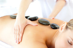 Blond woman having a stones massage Royalty Free Stock Photos