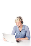 Blond Woman With Headset Looking At Laptop Stock Photo