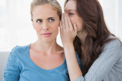 Blond woman hearing a secret from her friend Stock Photography