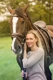 Blond woman and her horse in nature royalty free stock photography
