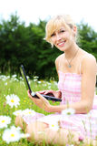 Blond woman with her laptop amongst daisies Stock Image