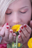 Blond woman hiding behind colorfoul flowers Stock Photos