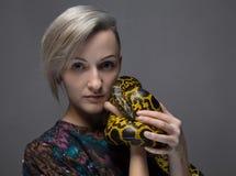 Blond woman holding anaconda Stock Image