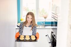 Blond woman holding a baking tray with freshly baked bread rolls. Royalty Free Stock Photo