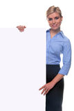 Blond woman holding a blank message board. An attractive blond woman holding a blank billboard looking towards camera, the board is a uniform color so you can Royalty Free Stock Photo