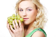 Blond woman holding a bunch of grape Royalty Free Stock Image