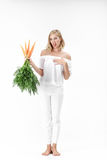 Blond woman holding carrot with green leaves on white background. girl feels bad from carrots and diets. Blond woman in a white blouse holding a carrot with stock photo