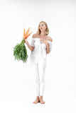 Blond woman holding carrot with green leaves on white background. girl feels bad from carrots and diets. Blond woman in a white blouse holding a carrot with royalty free stock photos