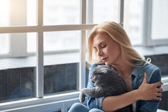 Blond woman holding cat near window. Royalty Free Stock Photos