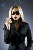 Blond woman holding a cigarette. Fashion style photo of a gorgeous blond woman holding a cigarette Stock Image