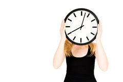 A blond woman holding a clock. In front of her face Royalty Free Stock Photo