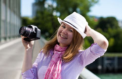 Blond woman holding cowboy's hat and camera Stock Images
