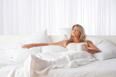 Blond woman holding cup of coffee. Lying on white bed Royalty Free Stock Photography