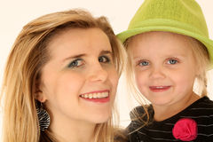 Blond woman holding a cute blond girl wearing a green hat Stock Images