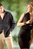 Blond woman holding glass with champagne, young man looking at s royalty free stock images