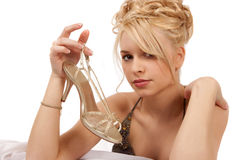 Blond Woman Holding A Gold Shoe. In Formal Clothing Stock Image