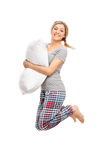 Blond woman holding a pillow and jumping. Vertical profile shot of a blond woman holding a pillow and jumping isolated on white background Royalty Free Stock Photo