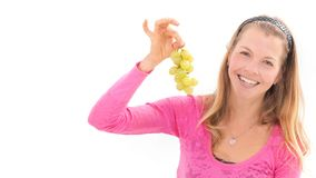 Blond woman holding ripe grapes, white background royalty free stock photography