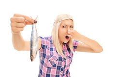 Blond woman holding a stinky fish Stock Photo