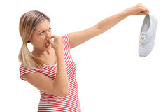 Blond woman holding a stinky shoe Stock Photo