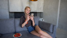 Blond woman holds mobile phone and eats ripe strawberry, sitting on soft sofa in living room with gray walls in