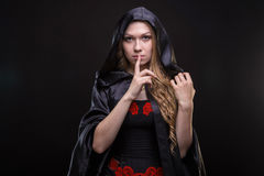 Blond woman in hood showing quiet gesture. On black background Stock Photography