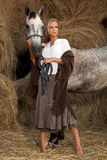 Blond woman with horse. Young blond woman with horse in barn, hay stack in background Stock Photos