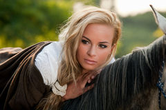 Blond woman on horse. Young blond woman resting on back of horse; countryside background Royalty Free Stock Photos