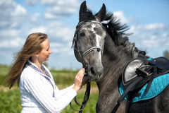 Blond woman with a horse Royalty Free Stock Image
