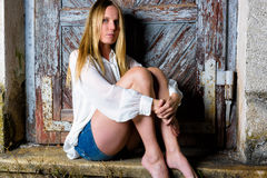 Blond woman in hot pants sitting in front of an weathered door Royalty Free Stock Photo
