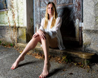 Blond woman in hot pants sitting in front of an weathered door Stock Images