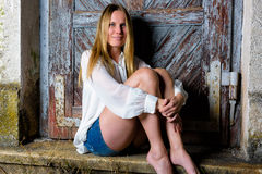 Blond woman in hot pants sitting in front of an weathered door Stock Photo