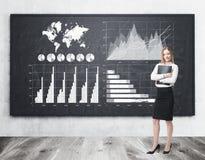 Blond woman hugging a folder near blackboard with graphs royalty free stock photo