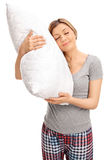 Blond woman hugging a pillow and sleeping. Vertical shot of a young blond woman hugging a pillow and sleeping isolated on white background Stock Image