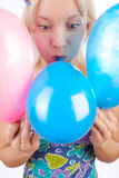 Blond woman inflating balloons Royalty Free Stock Image