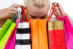 Blond woman inspecting content of colored paper bags with fresh. Buyings. Shopping, consumerism, delivery and present concept. Happy birthday and gifts concept Royalty Free Stock Images