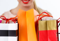 Blond woman inspecting fresh buyings. Packed in colored paper bags standing in front of her. Focus on bags. Shopping, consumerism, delivery and present concept stock photo