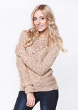 Blond  woman in  jeans and a beige sweater Royalty Free Stock Photography