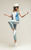 Blond woman jumping in hat and denim waistcoat Royalty Free Stock Photos