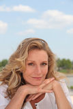 Blond woman by a lake. Blond woman relaxing by a lake Stock Photography