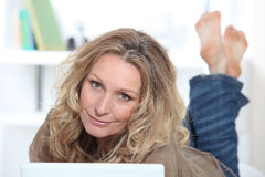 Blond woman on laptop. Blond woman working on laptop stock images