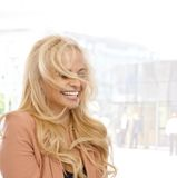 Blond woman laughing outdoors Royalty Free Stock Photography