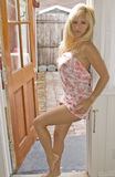 Blond Woman leaning against a Door Stock Photo