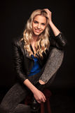 Blond woman in leather jacket resting her head on hand Royalty Free Stock Photo
