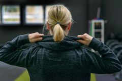 Blond woman lifting the hood of a top. Blond women lifting the hood of a top as she stands facing away in a gym in a close up head and shoulders view Royalty Free Stock Images