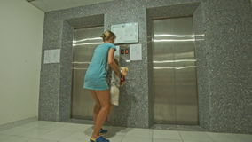 Blond Woman Lifts Little Girl to Press Button on Elevator stock footage