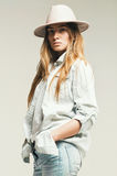 Blond woman in light blue denim shirt and hat Stock Photo