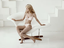 Blond woman in lingerie sitting ona modern design chair Royalty Free Stock Photo