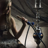 A blond woman in lingerie smoking a hookah Royalty Free Stock Photos