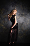 Blond woman in a long black evening dress Stock Photo